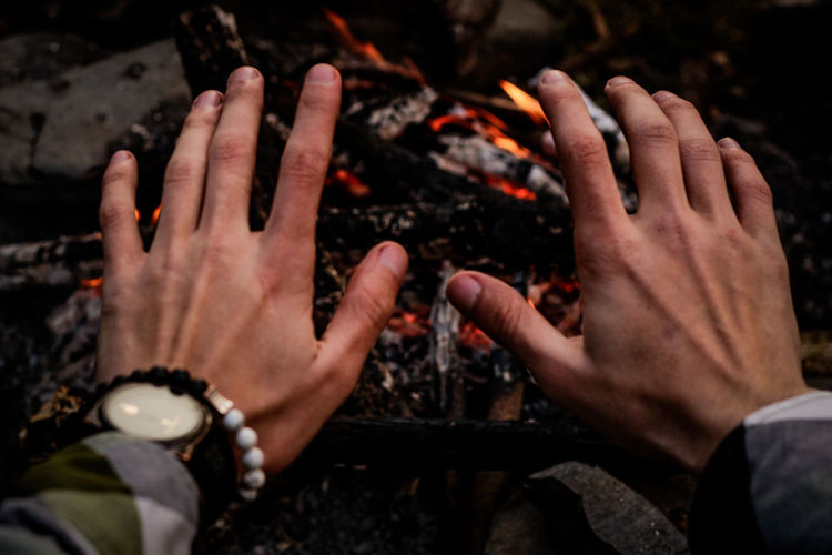 Cropped hands of man gesturing against campfire