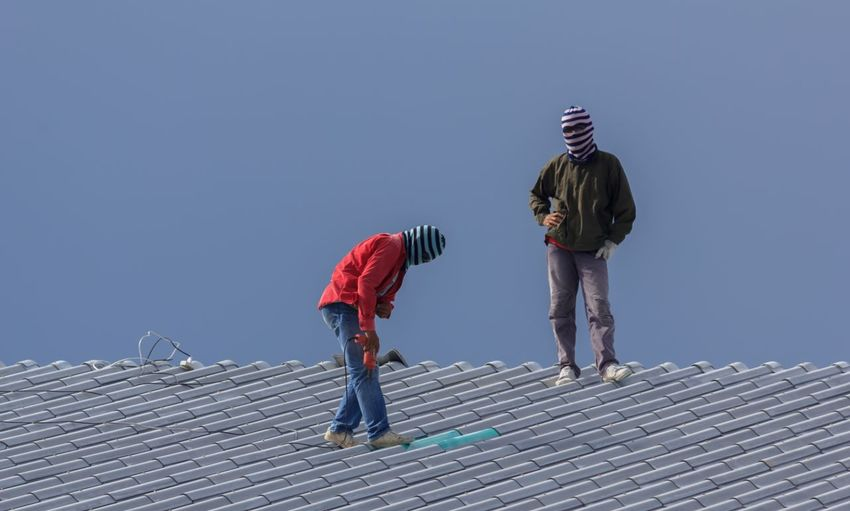 Low Angle View Of People On Rooftop Against Clear Sky