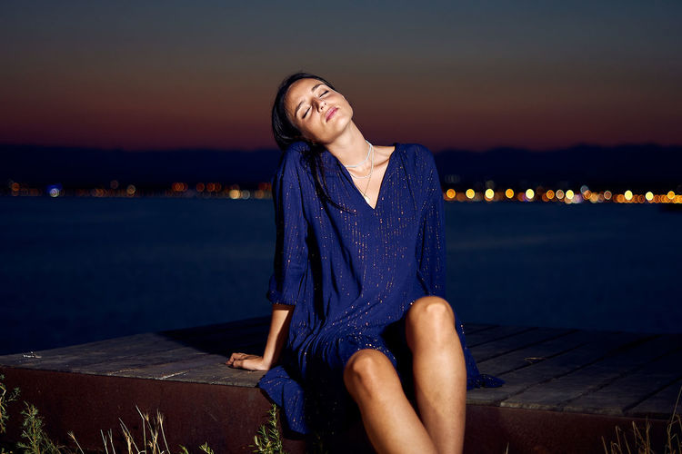 Young woman sitting against sea against sky during sunset
