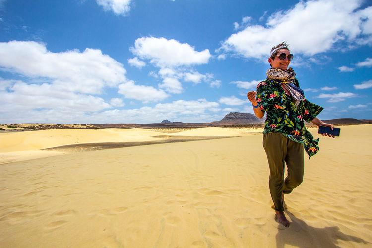 Woman standing on sand dune in desert against sky