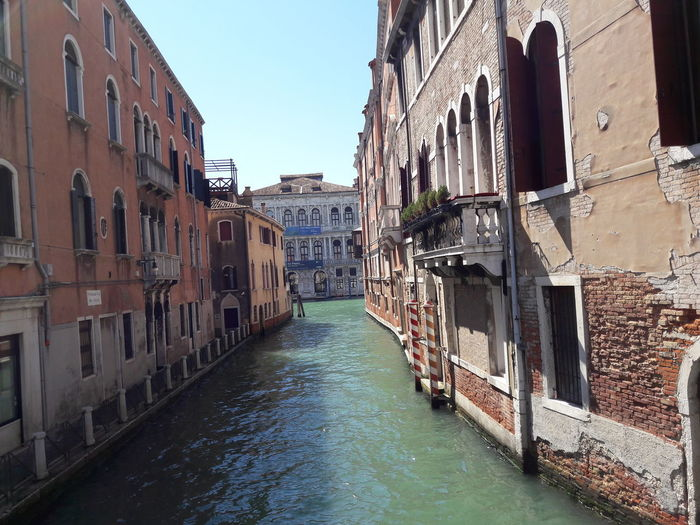 Canal passing through buildings against sky