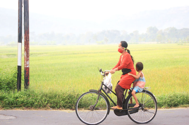 Boy riding bicycle on field