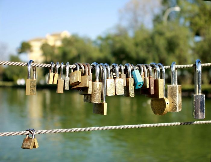 Close-up of padlocks hanging from railing against river