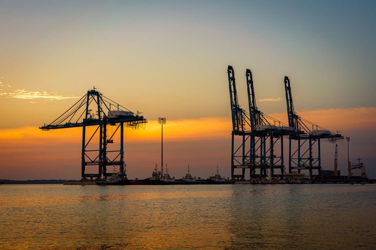 Silhouette cranes at commercial dock against sky during sunset
