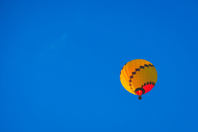Low angle view of hot air balloon in blue sky
