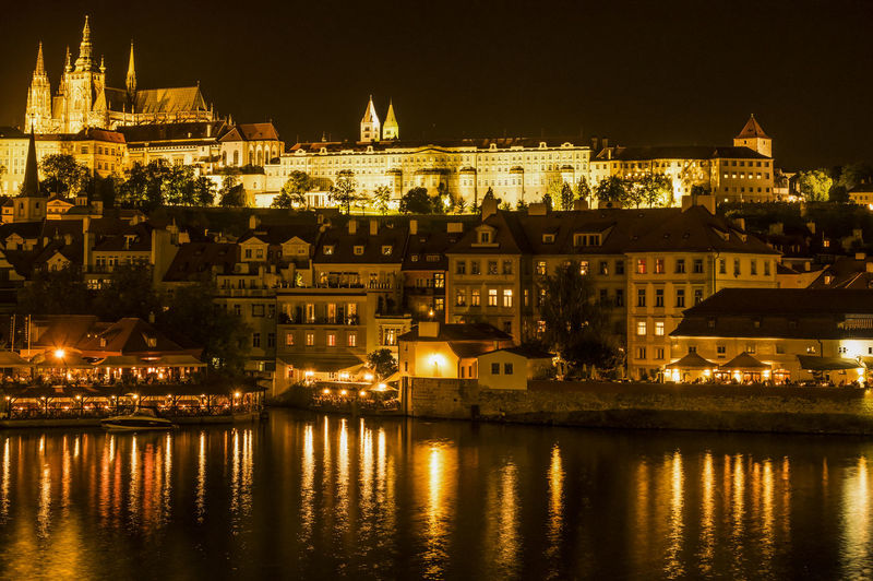 Illuminated cityscape by vltava river at night