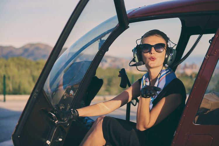 Attractive woman pilot sitting in the helicopter 30s Air Vehicle Aircraft Aircrew Aviator Beautiful Woman Benidorm Blowing Kisses Business Woman Cabin Crew Caucasian Female Flight Headphones Helicopter Inside Landing Field One Person People Pilot SPAIN Sunglasses Sunny Day Transportation Young Women