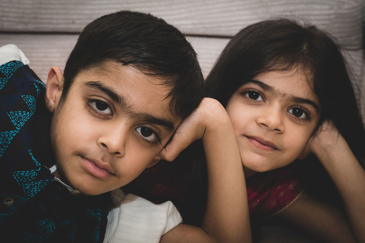 Close-up portrait of brother and sister at home