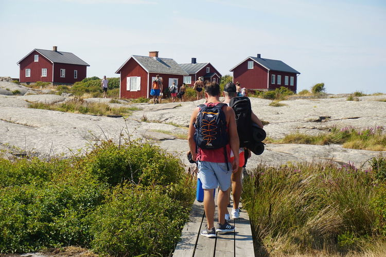 entering the Island of Hållö Travel Travel Destinations Tourist Attraction  Tourist Destination Summer Adventure Hiker Politics And Government Full Length Rear View Togetherness Childhood Walking Summer Sky Architecture Building Exterior Friend Human Back Backache Hiker Backpack