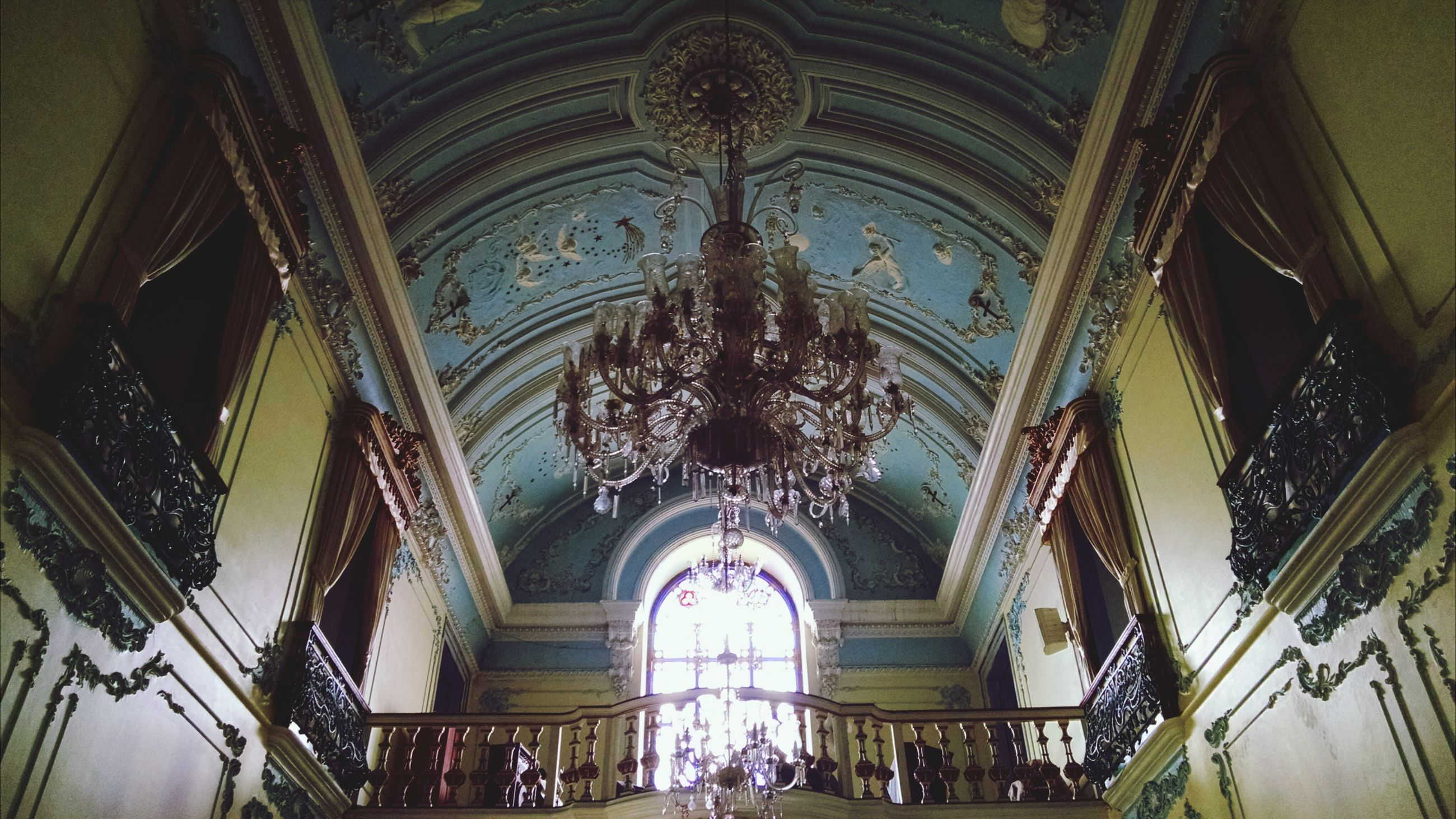 indoors, ceiling, architecture, built structure, low angle view, place of worship, arch, famous place, travel destinations, tourism, religion, illuminated, spirituality, person, large group of people, travel, men, interior, chandelier