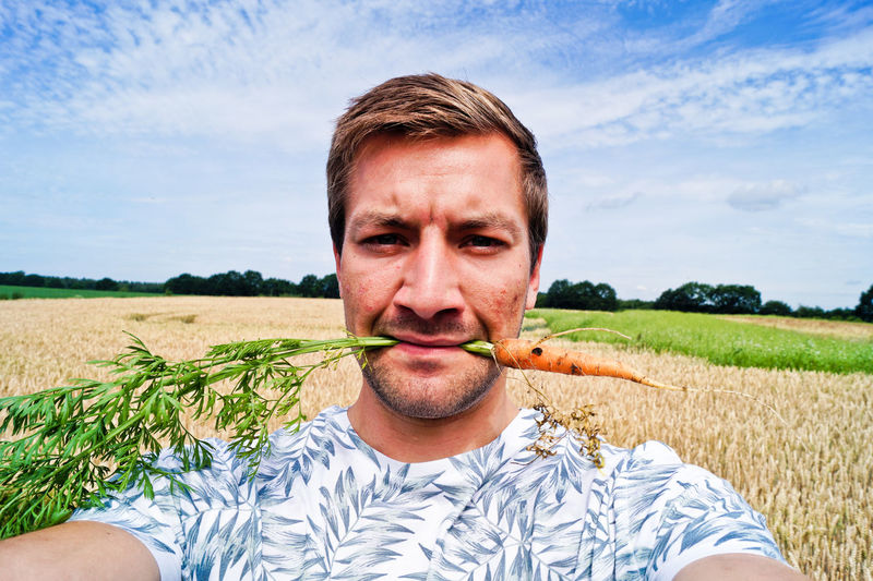 Portrait Of Man Holding Carrot In Mouth On Agricultural Field Against Sky