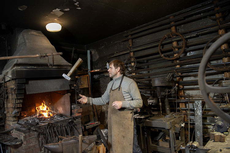 A blacksmith throws a hammer in his workshop