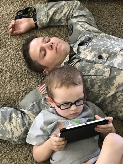 Father and Son Bonding Boys Childhood Communication Day Digital Tablet Elementary Age Family Family With One Child Father High Angle View Holding Learning Leisure Activity Lifestyles Looking Down Lying Down Men Playing Portable Information Device Real People Son Technology Togetherness Wireless Technology