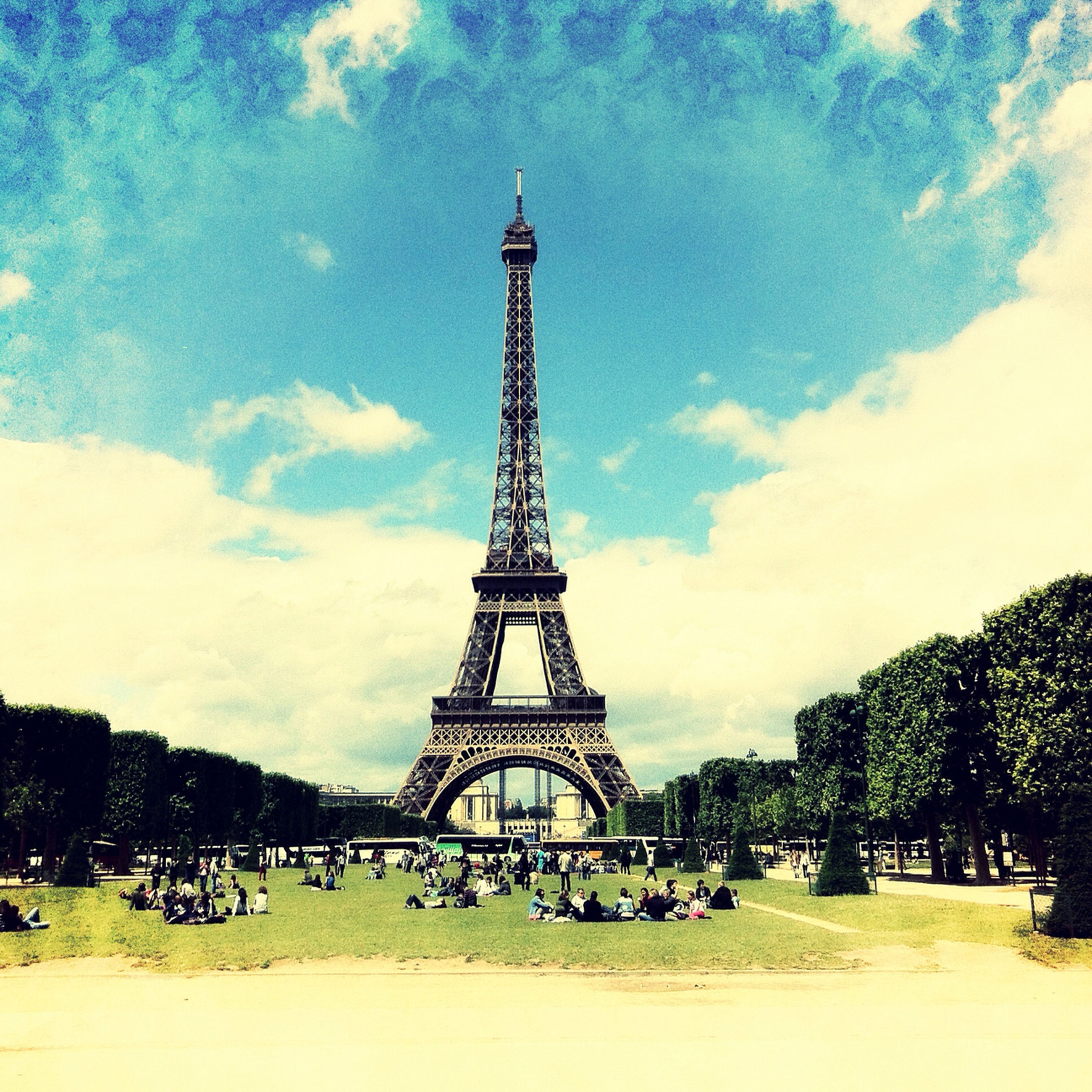 sky, architecture, famous place, eiffel tower, built structure, cloud - sky, tree, international landmark, travel destinations, tourism, tower, history, culture, travel, capital cities, grass, tall - high, cloud, cloudy, metal