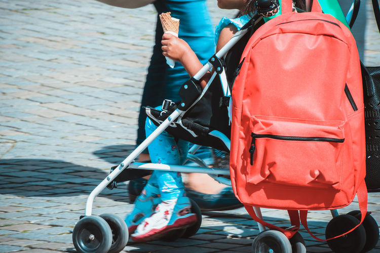 Low Section Of Girl Sitting On Baby Carriage
