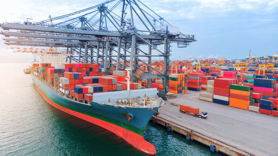Aerial of cargo container ship carrying container under big crane loading cargo import and export
