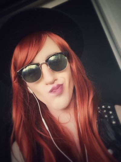 Smiling Young Woman With Redhead Wearing Sunglasses Listening To Music