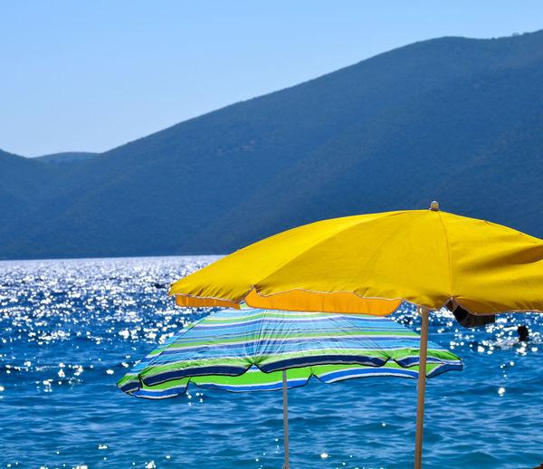 Yellow umbrella on beach against clear blue sky