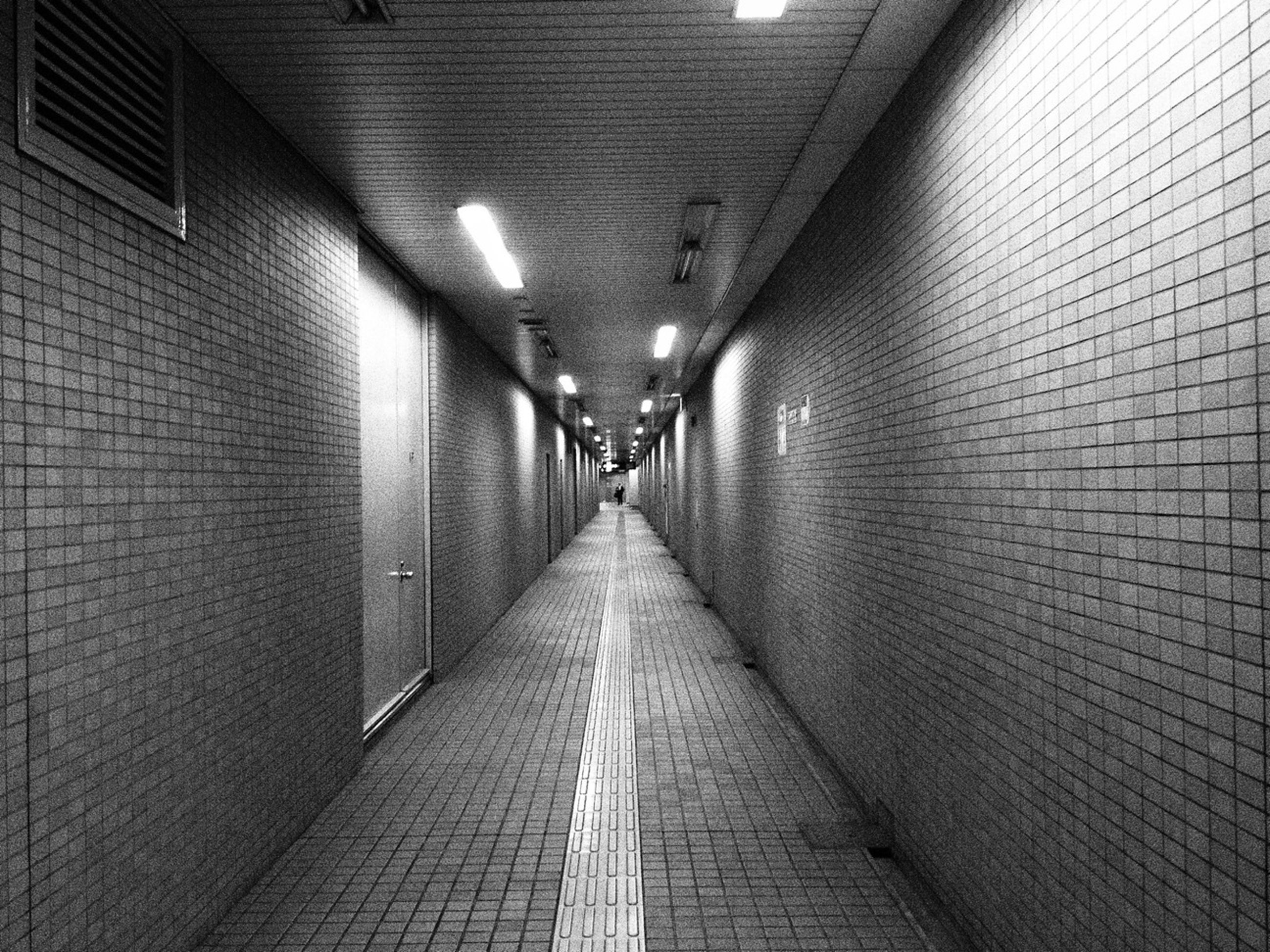 indoors, illuminated, the way forward, diminishing perspective, lighting equipment, ceiling, architecture, built structure, tunnel, corridor, wall - building feature, vanishing point, wall, electric light, pattern, empty, reflection, one person, light - natural phenomenon