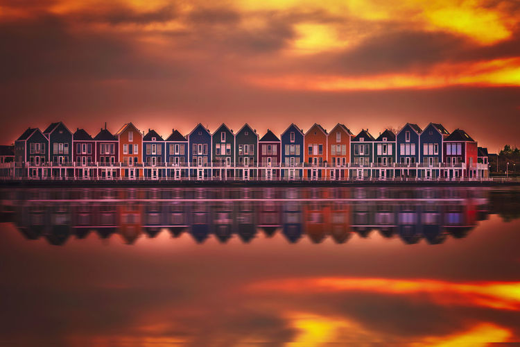 Reflection of building in sea during sunset