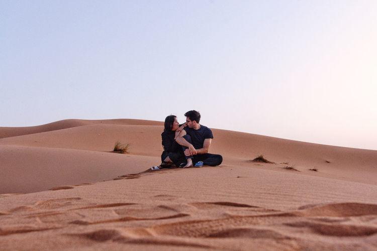 Couple on sand dune in desert against clear sky