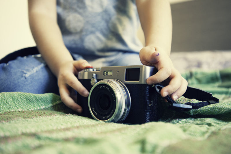 Midsection of girl holding camera on bed