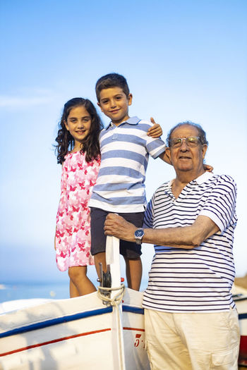 Grandfather with grandchildren on boat against sky