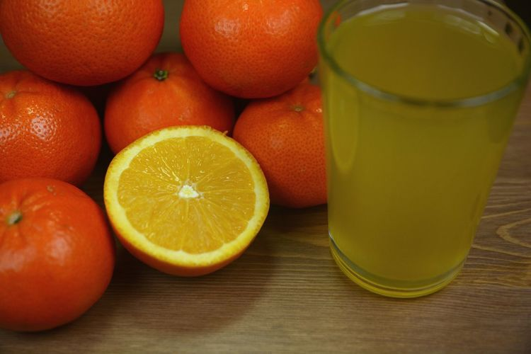 High Angle View Of Orange Fruits And Juice In Glass On Table