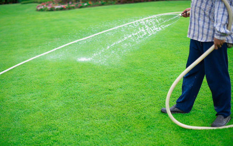 Low Section Of Man Watering With Garden Hose At Park