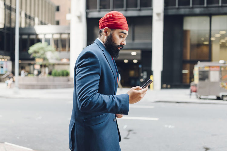 Man looking at camera while standing on street in city