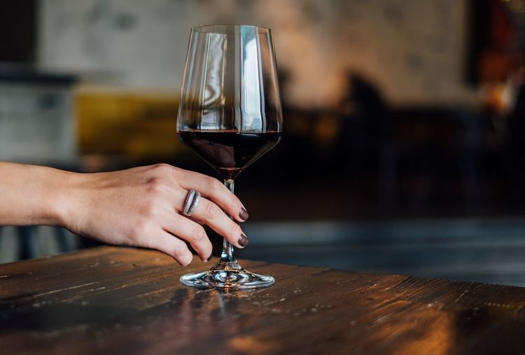 Woman holding glass of red wine Wineglass Wine Human Hand Table Red Wine One Person Real People Indoors  Close-up Drink Refreshment Food And Drink Human Body Part Alcohol Holding Focus On Foreground Copy Space Wine Tasting Elégance Accesories