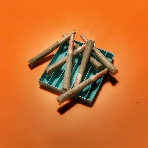 High angle view of cigarette on table against orange background