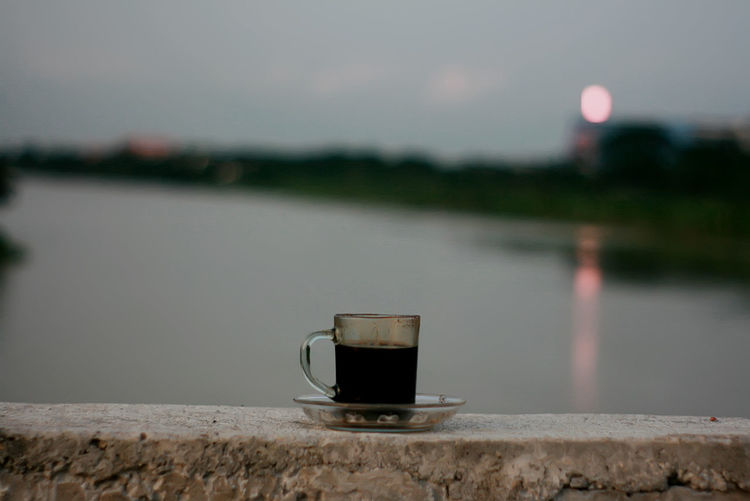Close-up of coffee cup against lake