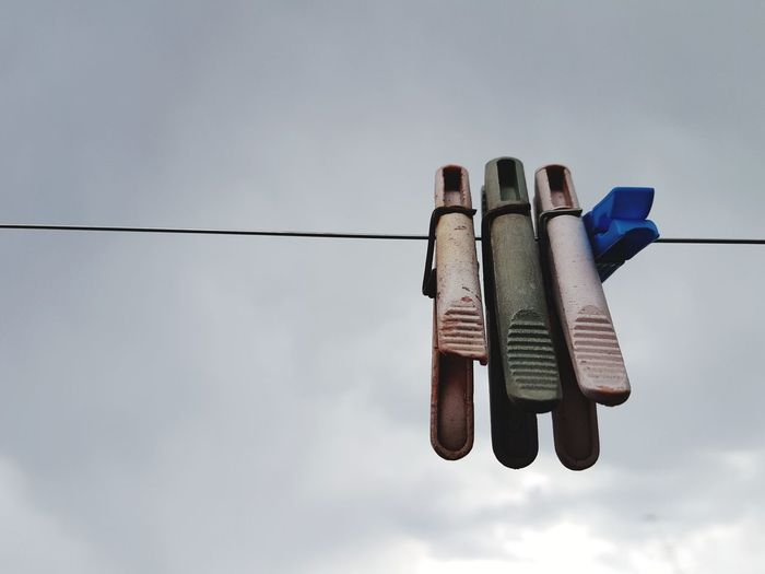 Low angle view of clothespins hanging on rope against sky