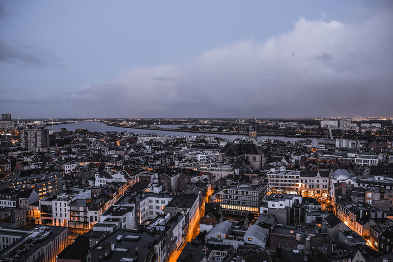 High angle view of illuminated city against cloudy sky