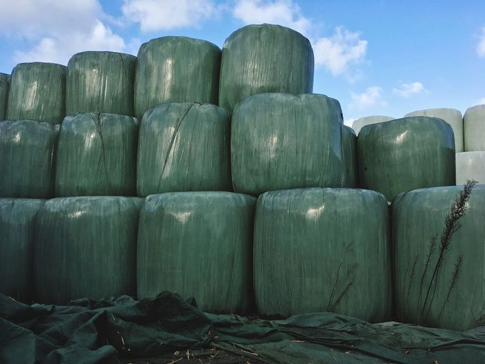 Hay bales in plastic arranged against sky at farm