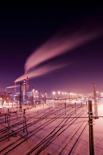 Smoke emitting from smoke stacks by railroad tracks at night