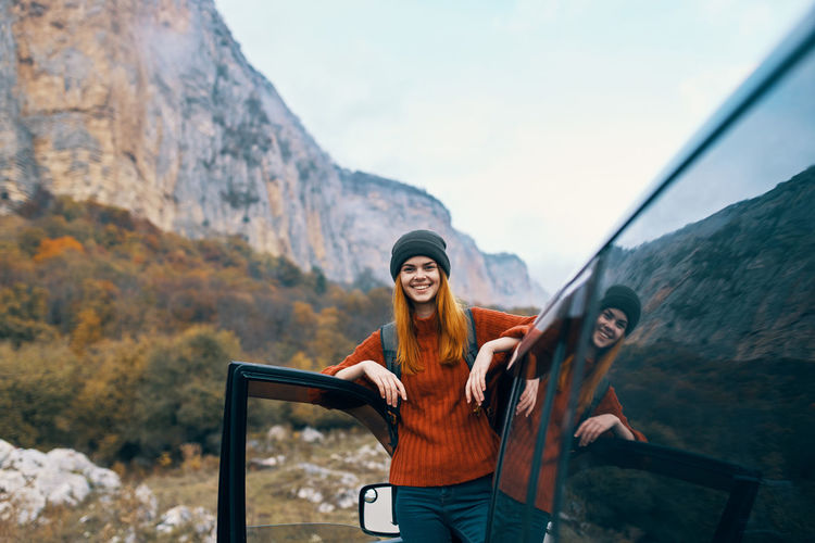 Portrait of smiling young woman standing on mountain