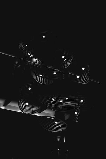 High angle view of illuminated lighting equipment on table against black background