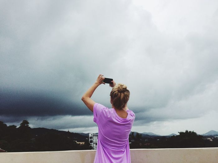 Rear view of woman photographing sky through mobile phone