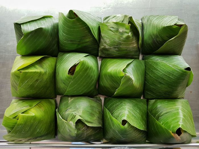 Directly above shot of wrapped food in leaves on table