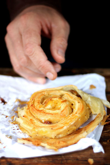 Close-up of hand reaching for pastry