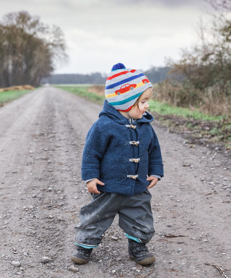Toddler girl on footpath – Kempen, Germany Adventure Baby Babyhood Bare Tree Boots Cardigan Cardigan Sweater Caucasian Cheerful Coat Duffle Coat Curiosity Cute Dirty Messy Muddy Exploring Field First Steps Footpath Front View Germany Girl Girls Females Happiness Happy Hiking Hikingadventures Jacket Joy Knit Hat Looking Down Mud Pants Mud Pants People Portrait Dirt Road Rural Scene Sweater Toddler  Toddlerlife Walking Wanderlust Watching Winter Wool Diminishing Perspective Healthy Lifestyle Child Childhood One Person Road Casual Clothing Males  Men Boys Standing Day Clothing Transportation Full Length Innocence Nature Tree Plant Focus On Foreground Hat Outdoors Jeans