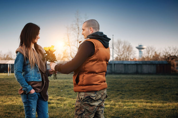 Women's Day Adult Bonding Casual Clothing Couple - Relationship Flower Grass Hairstyle Heterosexual Couple Men Nature Outdoors People Plant Positive Emotion Rosé Sky Standing Sunset Three Quarter Length Togetherness Two People Women Yellow Young Adult