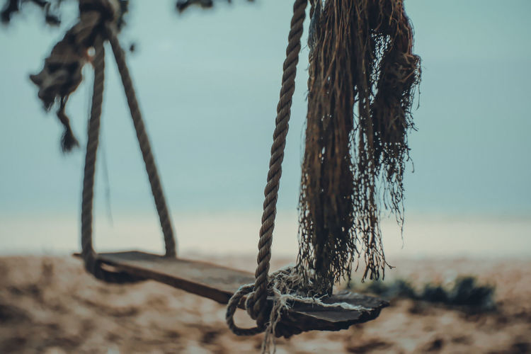 Close-up of swing hanging on rope at beach against sky