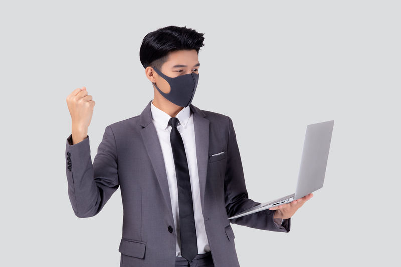 Young businessman wearing mask holding laptop against white background
