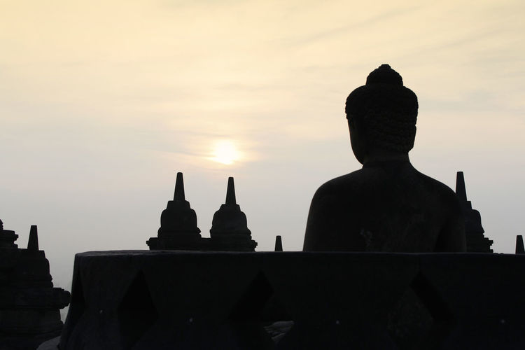 Silhouette Borobudur Temple with the Buddha statue during sunrise, Yogyakarta, Indonesia Borobudur Temple Yogyakarta Ancient Civilization Architecture Art And Craft Belief Buddhism Building Built Structure Dawn History No People Outdoors Place Of Worship Religion Sculpture Silhouette Sky Spirituality Statue Sunrise The Past Tourism Travel Destinations