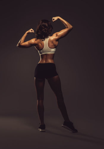 Athletic woman showing back and biceps muscles. Full length, studio shot Athlete Athletic BicepsAndTriceps Bodybuilding Figure Attractive Beauty Biceps Brunette Fitness Fitness Model Full Length Muscles Muscular Build One Person Physique  Sport Sportive Standing Strength Strong Studio Shot Women Young Adult Young Women