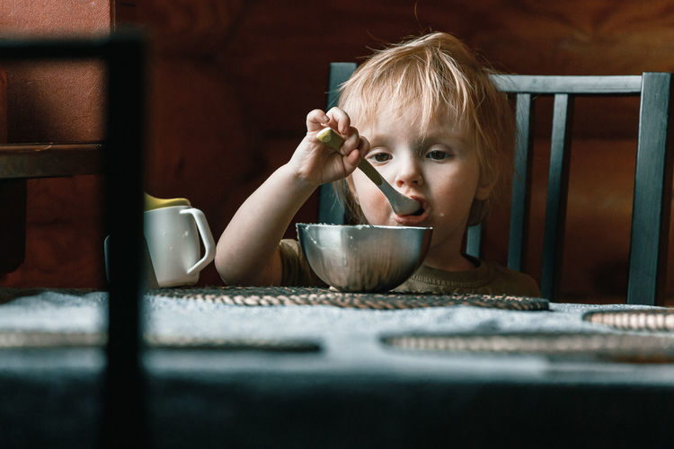 Portrait of cute baby girl in bowl on table