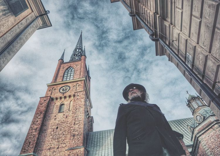 Low angle view of man standing by buildings against sky
